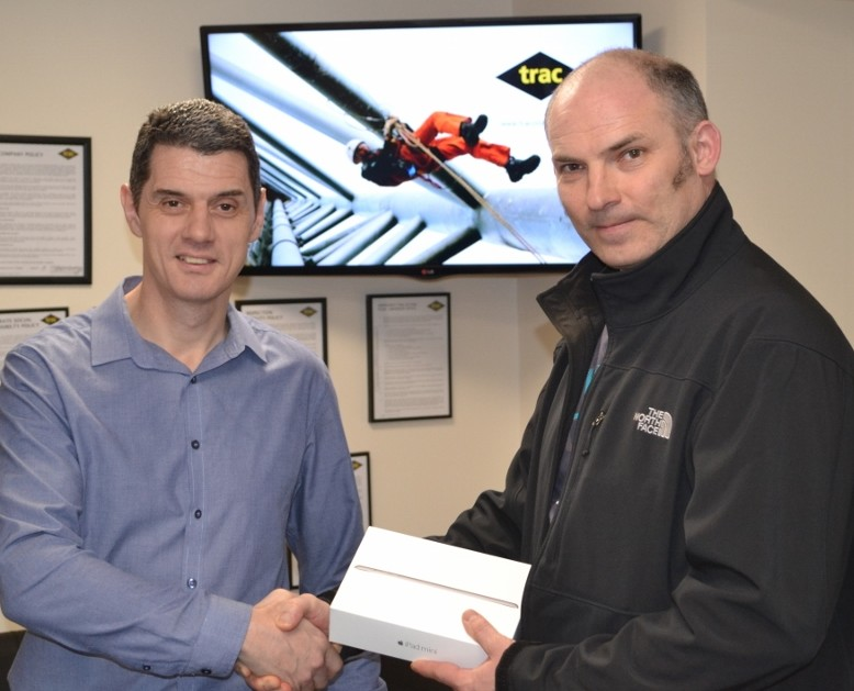 L-R: TRAC's Allan Robertson presents Team Leader Garry McFadden with an iPad for the contract service award, 5 other field staff were also recipients